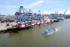 Blick auf HHLA Container Terminal Burchardkai - Containerschiffe liegen unter Containerbrücken, dahinter das Containerlager. Das Fahrgastschiff / Schaufelraddampfer Louisiana fährt durch den Waltershofer Hafen.