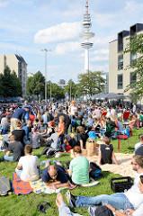 Grillfest von AnwohnerInnen und Flüchtlingen im Hamburger Karoviertel. Wiese am Tschaikowsky-Platz - im Hintergrund der Hamburger Fernsehturm.