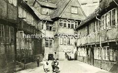 Historische Bilder aus dem Hamburger Gängeviertel - Hinterhof in der Steinstrasse, Kinder spielen in der Sonne, Wäsche hängt zum Trocknen auf der Leine.