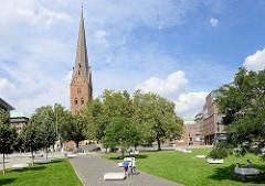 Blick über den Domplatz zur Hamburger St. Petrikirche; Steinblöcke / Quader laden zum Sitzen ein.