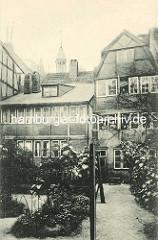Historische Bilder aus dem Hamburger Gängeviertel - Hinterhof mit Garten, Büsche und Blumen - Großer Bäckergang; im Hintergrund die Kuppel der St. Michaeliskirche / Michel.