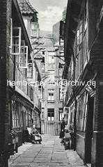Historische Bilder aus dem Hamburger Gängeviertel - Krameramtswohnungen im Krayenkamp - die Fenster sind geöffnet - eine Frau sitzt mit einer Zeitung im Stuhl - eine weitere steht in der geöffneten Tür.