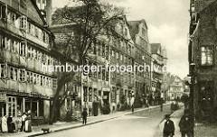 Historische Bilder aus dem Hamburger Gängeviertel - Geschäfte, Lederhandlung in der Strasse Teilfeld - Blick vom Herrengraben; Frauen mit Schürze auf der Strasse, Hund und Passanten auf dem Bürgersteig.
