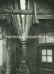 Alte Fotos aus dem Gängeviertel Hamburgs - Gang im Kornträgergang, die Mauern / Hauswände sind mit Holzbalken abgestützt.