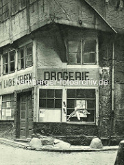 Alte Fotos aus dem Gängeviertel Hamburgs - Drogerie Ecke Kornträgergang und Rademachergang; Aufschrift Lacke, Seifen - Gulliedeckel und Prellsteine.