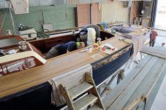 Der Rumpf des Neubaus ist lackiert - Detailarbeiten beim Innenausbau des Daysailers.