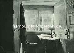 Alte Fotos aus dem Gängeviertel Hamburgs - Wohnzimmer im Langen Gang; Tisch mit gedrechselten Beinen, Zeitung und Öllampe; Blick aus dem Fenster auf die gegenüber liegende Hauswand.