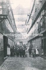 Historische Bilder aus dem Hamburger Gängeviertel - eine grosse Gruppe von Schulkindern stehen auf dem Kopsteinpflaster vom Blauen Lappen; Mädchen tragen weisse Schürzen.