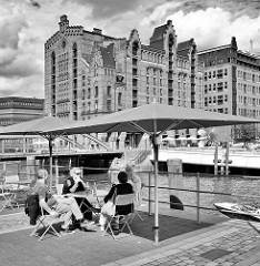 Cafe am Ufer des Magdeburger Hafens in der Hamburger Hafencity - im Hintergrund der ehem. Kaispeicher B, das jetzige Hamburger Maritime Museum.