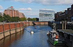 Zwei Sportboote fahren auf dem Zollkanal; die Motorboote kommen vom Oberhafen und haben gerade den Wandrahmsteg passiert. Das ehem. Zollschiff Oldenburg liegt am Ponton des Deutschen Zollmuseums in der Hamburger Speicherstadt. Links hinter der Ka