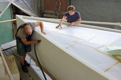 Abkleben des Schiffsdecks - Absaugen der Bordwand mit Staubsauger und Bürste; Vorbereitungsarbeiten für die Bootslackierung.