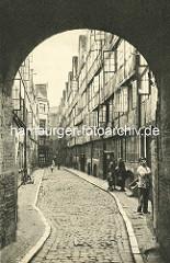 Historische Bilder aus dem Hamburger Gängeviertel - Blick durch die Toreinfahrt in den Paradieshof; Kinder spielen auf der Strasse, zwei Frauen mit Kind unterhalten sich.