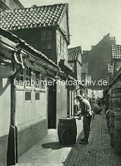Historische Bilder aus dem Hamburger Gängeviertel - Arbeiter, Fassmacher / Küfer mit Hammer an einem Faß, weitere Fässer sind an der Wand aufgestapelt.