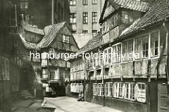 Historische Bilder aus dem Hamburger Gängeviertel - Hinterhof im Schulgang - hohe Mietshäuser, Fachwerkhäuser - eine Frau sitzt vor der Tür.