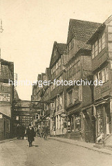 Historische Bilder aus dem Hamburger Gängeviertel - Blick in die Mohlenhofstrasse; Passanten - Mann mit Zylinder, Schilder von Ladengeschäften / Hund auf der Treppe. Die Häuser sind wegen Baufälligkeit quer über die Strasse mit Trägern abgestütz