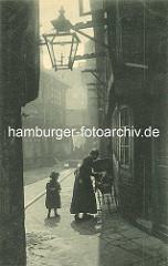 Historische Bilder aus dem Hamburger Gängeviertel - schmaler Gang bei der Steinstrasse; Mutter mit Kind und Kinderwagen - Gaslaterne an der Hauswand, Holzgestelle zum Wäschetrocknen vor den Fenstern.