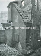 Alte Fotos aus dem Gängeviertel Hamburgs - Treppenaufgang zum Dachgeschoss, Aussentoiletten im Hof - Kopfsteinpflaster.