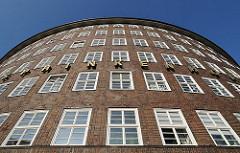 Architekturbild von der runden Ecke des Hamburger Kontorhauses Sprinkenhof Buchardstrasse / Johanniswall; in Goldbuchstaben steht der Name SPRINKENHOF an der Fassade des Bürogebäudes.