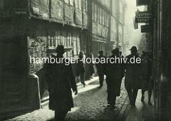 Alte Fotos aus dem Gängeviertel Hamburgs -  Männer mit Hut Ecke Langer Gang / Kornträgergang - Frauen haben sich wartend an die Hauswand gelehnt.