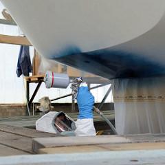 Lackierung des Schiffsrumpfs vom Daysailer - der Lackierer trägt Schutzanzug und Atemmaske - der Schiffsboden ist abgeklebt.