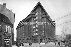 Kontorhaus Chilehaus im Hamburger Kontorhausviertel - Passanten auf der Strasse; re. im Hintergrund der Kirchturm der St. Petrikirche.