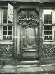 Alte Fotos aus dem Gängeviertel Hamburgs - Barocktür mit aufwändigen Dekorschnitzereien im Rademachergang; Schild Altpapier, Lumpen Eisen