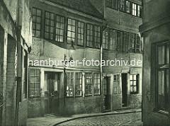 Alte Fotos aus dem Gängeviertel Hamburgs - Nachtaufnahme im Langen Gang, Gaslaterne / beleuchtete Fenster.