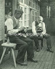 Historische Bilder aus dem Hamburger Gängeviertel - zwei Männer sitzen auf Holzbänken in der Sonne vom Breiten Gang; einer reinigt seinen Hut mit einem Lappen - auf der Leine hängen zwei Damenstrümpfe.