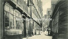 Historische Bilder aus dem Hamburger Gängeviertel - Gruppenfoto von Hausfrauen mit Schürze im Druvenhof - Haustür mit Barockschnitzereien - Gardinen und Blumen im Fenster.