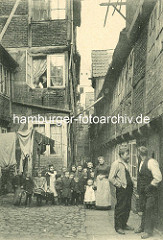 Historische Bilder aus dem Hamburger Gängeviertel - Gruppenbild im Scheeben Steebel, Jungen und Mädchen stehen in dem Gang, zwei Männer unterhalten sich - ein Ehepaar blickt aus dem Fenster; Wäsche / Hemden hängen zum Trocknen über der Strasse.