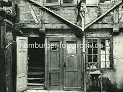 Alte Fotos aus dem Gängeviertel Hamburgs - Eingänge im Hinterhof, Rademacher Gang; schmale Holztüren, Fenster mit Gardinen - Wasserhahn an der Hauswand.