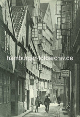 Alte Fotos aus dem Gängeviertel Hamburgs -  Mutter mit Kind, Briefträger im Kornträgergang; Schild Annahme Wäsche aller Art.