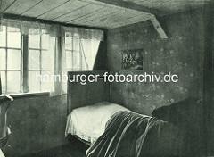 Historische Bilder aus dem Hamburger Gängeviertel - Schlafzimmer, Bett mit Decke im Langen Gang; Gardinen am Fenster, Papierbild an der Wand.
