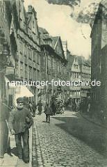 Historische Bilder aus dem Hamburger Gängeviertel - Wohnhäuser, Geschäftshäuser in der Düsternstrasse; Mann mit Bart und Mütze, Pferdegespann und abgestellte Handkarre auf dem Strassenpflaster.