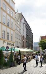 Hamburger Deichstrasse - Aussengastronomie; Tische unter Sonnenschirmen im Freien;  historische Bürgerhäuser am Nikolaifleet als Touristenattraktion.