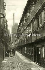 Historische Bilder aus dem Hamburger Gängeviertel - Wohnhäuser im Brauerknechtsgraben - Gruppenfoto, Frauen sehen aus dem geöffneten Fenster - Fabrikschornstein.