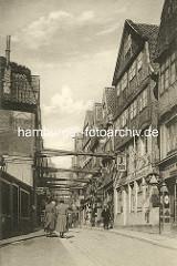 Historische Bilder aus dem Hamburger Gängeviertel - alte Häuser in der Mohlenhofstrasse - die Gebäude werden mit Balken quer über die Strasse gestützt.