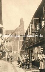 Historische Bilder aus dem Hamburger Gängeviertel - Gruppe von Kindern auf dem Kopfsteinlpflaster - zwei Väter haben ihre Kinder auf dem Arm, eine Frau trägt ihren Hund.