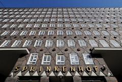 Fassade des Hamburger Kontorhauses Sprinkenhof, der Schriftzug steht in goldenen Lettern über dem Eingang.