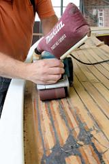 Mit einem Bandschleifer und groben Schleifpapier wird die überschüssige Fugenmasse vom Mahagoniedeck des Daysailers abgeschliffen.