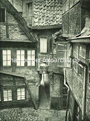 Alte Fotos aus dem Gängeviertel Hamburgs - Blick in den Langen Gang, Gaslaterne; Regenrinne mit Abflussrohr.