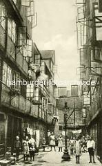 Historische Bilder aus dem Hamburger Gängeviertel - Kinder, Jungen und Mädchen in der Springeltwiete, geöffnete Fenster - Bettwäsche zum Lüften, Gaslaterne.