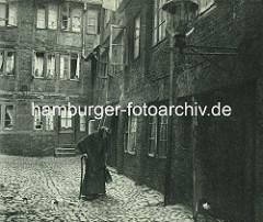 Historische Bilder aus dem Hamburger Gängeviertel - eine alte Frau mit Kopftuch und Stock geht über das Pflaster vom Kornträgergang.