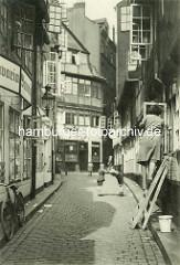 Historische Bilder aus dem Hamburger Gängeviertel - Kinder spielen auf dem Kopfsteinpflaster - eine Frau steht auf der Leiter und putzt Fenster - ein Fahrrad lehnt an der Hauswand einer Kneipe / Bavaria Bier Werbung.
