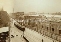 Historische Ansicht der Großen Elbstraße in Altona - geschlossene Güterwaggons stehen auf den Gleisen der Hafenbahn - die Lagerschuppen sind mit einem hohen Zaun gesichert. Im Hintergrund die Elbe und Helgen der Hamburger Werften.grosse-elbstrass