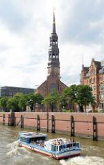 Eine Barkasse mit Touristen an Bord bei einer Hafenrundfahrt im Zollkanal - im Hintergrund der Kirchturm der St. Katharinenkirche.
