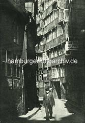 Alte Fotos aus dem Gängeviertel Hamburgs -  Mann mit Anzug und Weste, Schirmmütze im Kornträgergang; Schild Gasthaus, Logierhaus.
