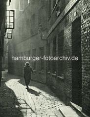 Alte Fotos aus dem Gängeviertel Hamburgs -  eine Frau geht im Gegenlicht über das Kopfsteinpflaster im Großen Trampgang.