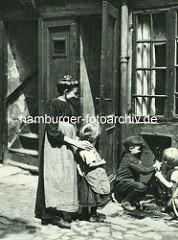 Historische Bilder aus dem Hamburger Gängeviertel - Kinder spielen im Rademachergang - die Mutter sieht zu.