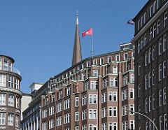 Hausfassaden im Hamburger Kontorhausviertel an der Strassenkreuzung Schopenstehl, Niedernstrasse und Kattrepel; auf dem Dach des Bürogebäudes Montanhof weht die Hamburg Fahne - dahinter die Spitze vom Kirchturm der Hamburger Hauptkirche St. Jakob